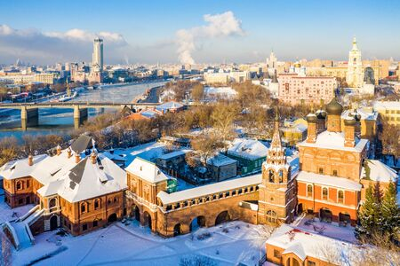 Moscow, Russia - 29 Dec 2018: Winter view of Moskva river, Novospasskiy Bridge, and skyscrapers on a sunny morning. Krutitsy Metochion. Ice, snow on roofs and streets. White Christmas, New Year's eve Editoriali