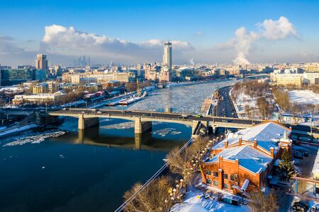 Moscow, Russia - 29 Dec 2018: Winter view of Moskva river, Novospasskiy Bridge, and skyscrapers on a sunny morning. Ice floes, blocks of ice, snow on roofs and streets. White Christmas, New Year's eve