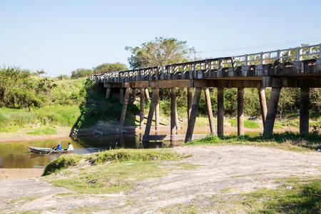 National Route 9 highway runs over a river bridge in Paraguayan Gran Chaco savannah, Paraguay. Ruta Nacional Numero 9 Dr. Carlos Antonio Lopez. Ruta Transchaco. Two men in a rowing boat. Archivio Fotografico