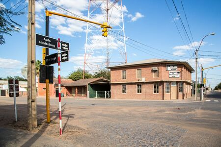 FILADELFIA, PARAGUAY - July 15, 2018: City centre of Filadelfia, Boqueron Department, Gran Chaco, Paraguay. Deutsch mennonite colony. Traffic lights and street name signs on red-white pillar.