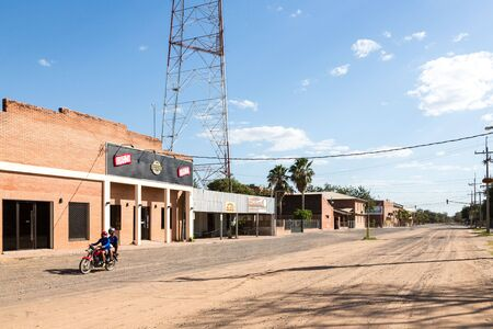 City centre of Filadelfia, Boqueron Department, Gran Chaco, Paraguay. Deutsch mennonite colony. Two guys on a bike driving down the sandy dusty street.