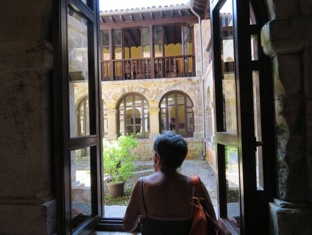The precious image of woman looking out the window at a convent