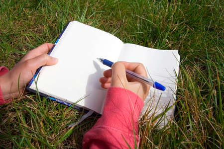 Woman writing in a blank book photo