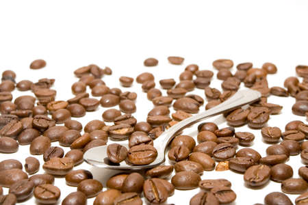 disposed: spoon with coffee beans randomly disposed isolated in white background