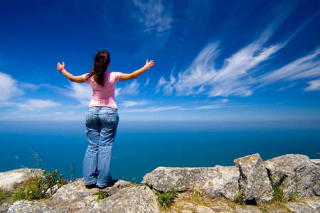 arms wide open: young woman with arms wide open contemplating the ocean Stock Photo