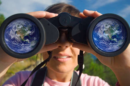 zoom earth: young woman with binoculars with the earth globe reflected in the lens Stock Photo