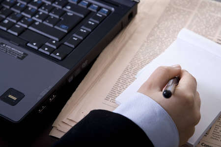 businesswoman in office with computer newspaper and notebook Stock Photo