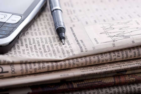 pile of financial newspapers with mobile phone and pen on top of it