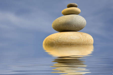 calmness: pile of zen round stones with blue sky and water reflexion