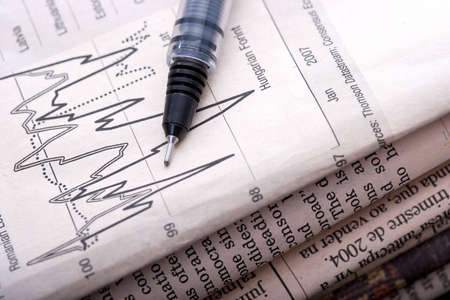 pen pointing to stock chart in economical newspaper Stock Photo