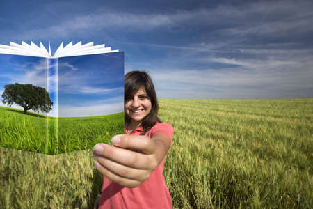 young woman smiling holding book with colorful cover photo