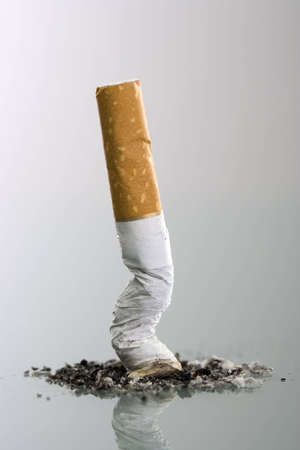 Cigarett butt end crushed into ashtray - grey background