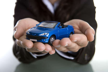car loans: businesswoman holding car in the hands - insurance or car business concept Stock Photo
