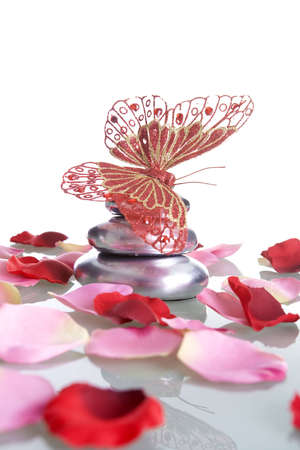 butterfly stationary: pile of stones with rose petals and butterfly - spa and zen concept Stock Photo
