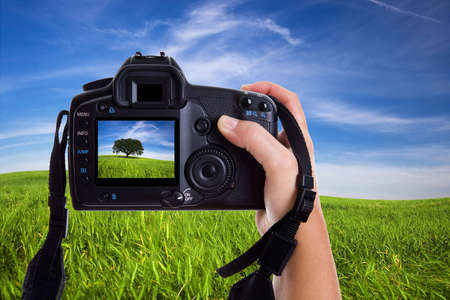 Woman photographing landscape with digital photo camera photo