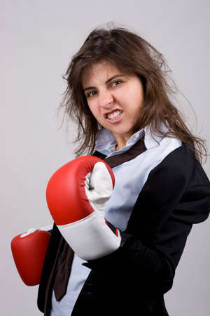 businesswoman wearing boxing gloves with confident attitude. grey background. photo