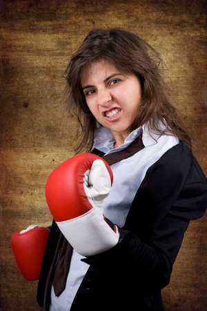 businesswoman with boxing gloves over grunge background photo