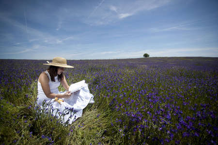 young woman in white dress reading book outdoors