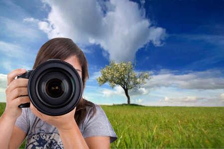 young female photographer with digital photo camera shotting landscape scene Stock Photo