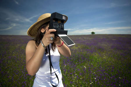 young woman with instant photo camera taking landscape pictures photo