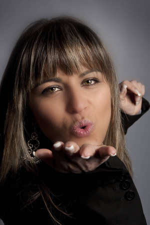 fashion model sending kiss portrait in grey background Stock Photo - 4862460