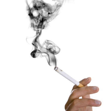 smoker hand holding cigarette - skull apearing in the smoke - health concept Stock Photo