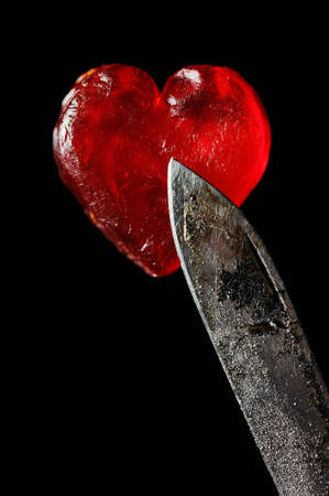 Red little heartand rusty knife, close-up shoot. Symbolises health hazard, for example danger of smoking photo