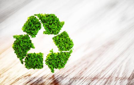 新鮮な緑の葉は、背景をぼかした写真木製机の上のシンボルをリサイクルします。3 D イラスト。