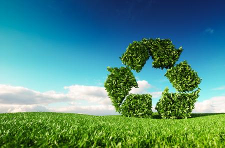 Umweltfreundliches Recyclingkonzept. 3D-Wiedergabe des grünen Recycling-Symbols auf frischer Frühlingswiese mit blauem Himmel im Hintergrund. Standard-Bild