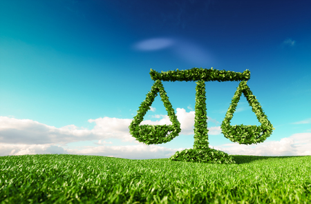 Eco friendly law, politics and eco balance concept. 3d rendering of scale icon on fresh spring meadow with blue sky in background. Foto de archivo