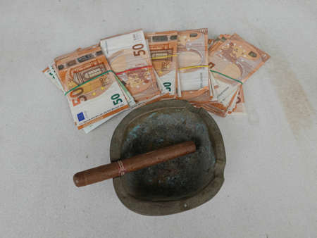 close-up of packs/bundles of money, dollars/euros with a cigar on a ashtray Stock Photo