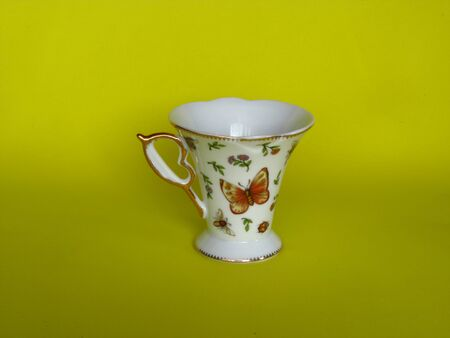 Empty cup with a pattern of butterflies on a yellow background