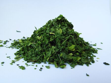 A bitter dried green parsley spice on a white background