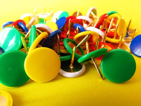 Multicolored buttons, cloves on a yellow background. Stationery nails for fastening paper.
