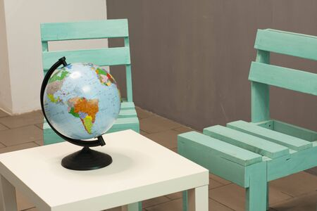 A coffee table and a wooden chair near a gray wall. Globe, travel agency office. Standard-Bild