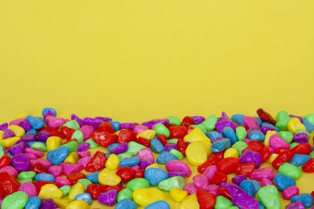 Multicolored decorative stones on a yellow background. Texture
