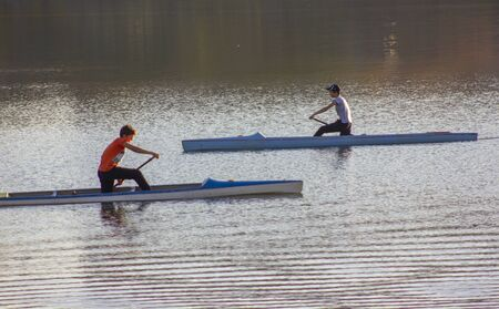 Children's canoe competitions on the river. Water and evening sun. Standard-Bild - 131748266