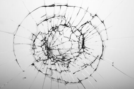 Cracked glass on white background texture. Broken glass. Cracks from impact or shot.