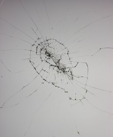 Black crack lines broken by vandals of glass on windows. Damaged shop window glass on a gray background.