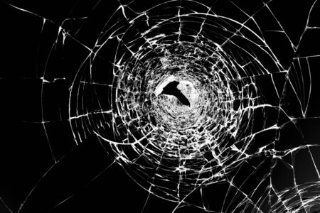 Cracks on broken glass after gun shots. Punched hole in windshield Vandalism and assault with a firearm. Damaged window robbers. Stock fotó - 138295354