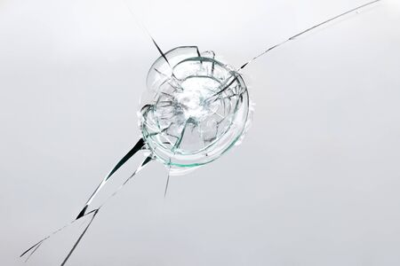 Broken window with cracks from impact or shot. Texture of cracks and chips on car windshield, concept for design on white background. Stock Photo
