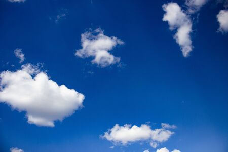 Blue sky and white fluffy clouds. Beautiful background for design or greeting card.