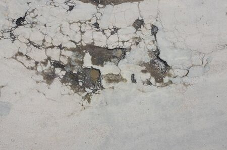 Pits with water after rain, cracks and broken asphalt, the road in need of repair.
