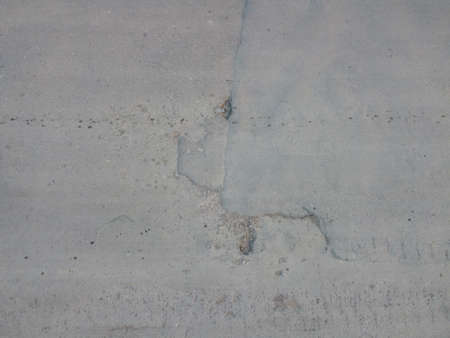 Potholes on the asphalt. Background of a broken road with potholes and restoration patches. Concept for design. The texture of the damaged road surface.