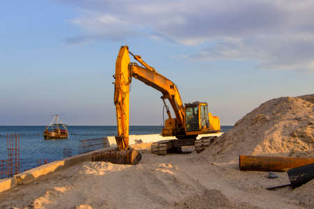 An excavator near the sea digs sand to build a beach on the coastal zone. Imagens