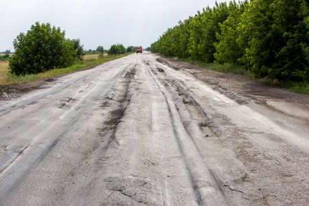Damaged road by truck. Asphalt pits from heavy trucks. Congestion on the road.