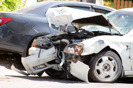 A road accident, a car that crashed, a white car on the road, cracks in the glass and a damaged bumper.