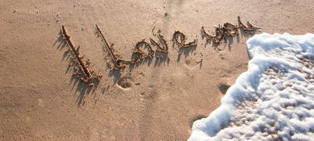 I love you - a love message on the golden sand with a wave that foams and washes away the inscription