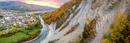 Autumn panorama, rock in the mountains, hills and mountain settlement by the river. Beautiful autumn landscape at sunrise. 免版税图像