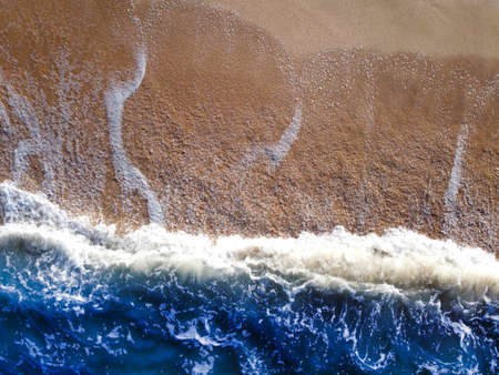 Blue wave and sand on the sea beach, top view.